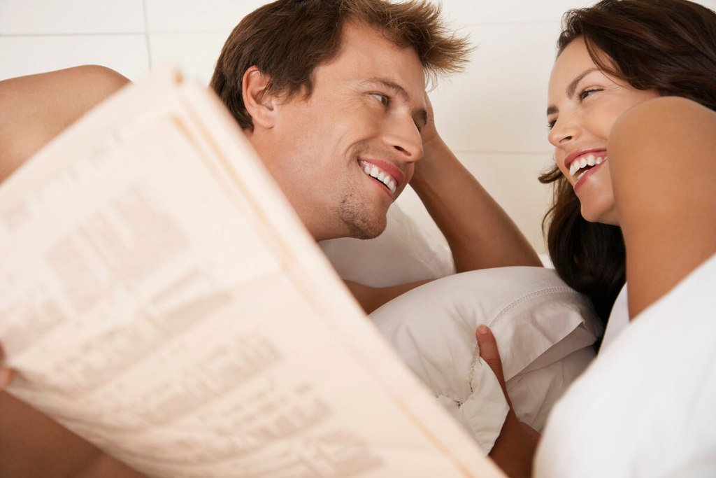 Woman laughing with her man while laying in bed