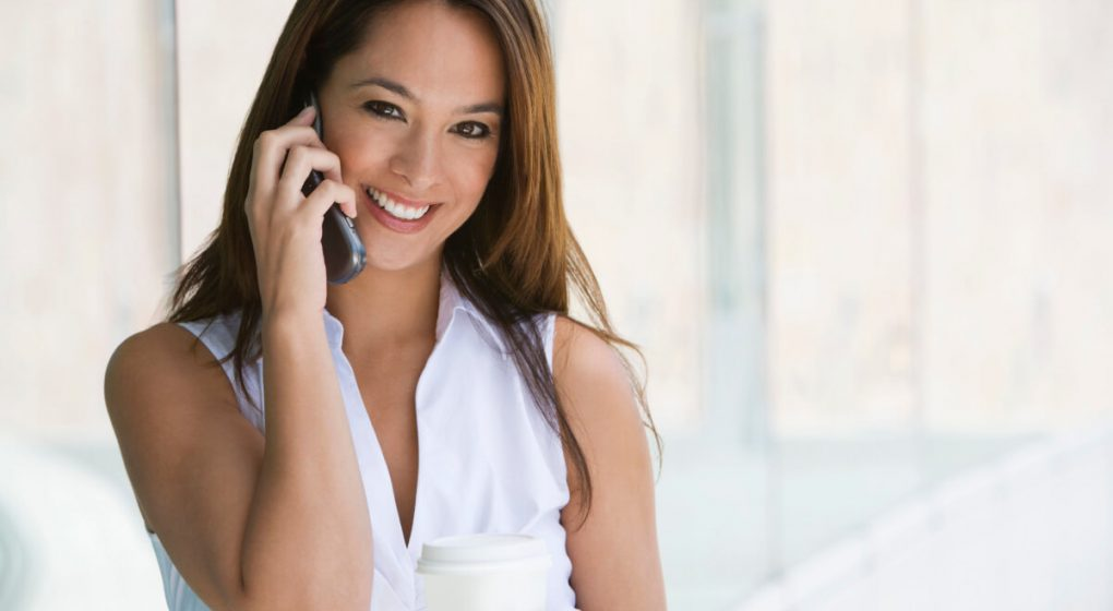 Smiling woman talking on the telephone to her man