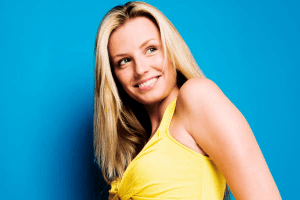 Blond woman in a yellow dress smiling seductively