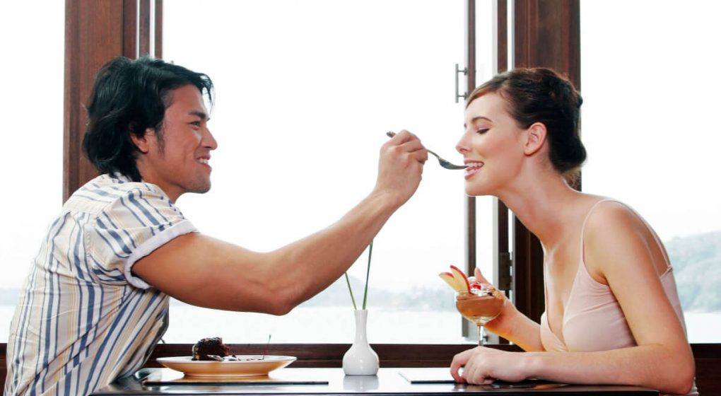 Gemini man offering woman food on a fork over the dining table.