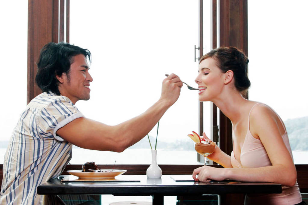 Gemini man offering woman food on a fork over the dining table