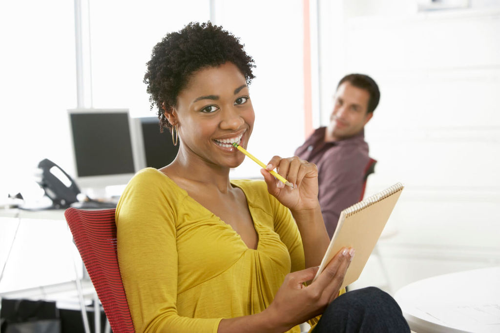 Smiling woman sitting with a pencil to her mouth being watched by a man