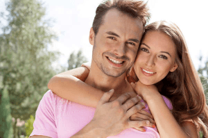 Woman with her arms around the shoulders of her Pisces man both smiling