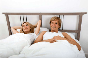 Libra man in bed with a woman in bed who has her hands behind her head