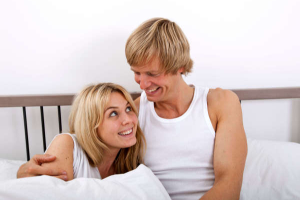 Scorpio man sitting up in bed with his arm around a smiling blond woman