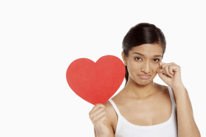 Sad woman holding a heart shape as she tries to work out how to win a Virgo man back after a breakup