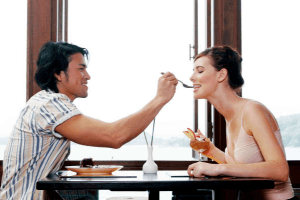 Taurus man offering food on a fork across a table to his partner
