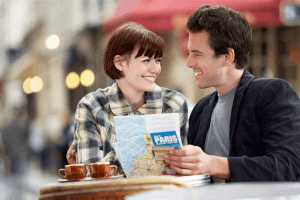 Woman smiling as she learns how to attract a Taurus man who is reading a map beside her