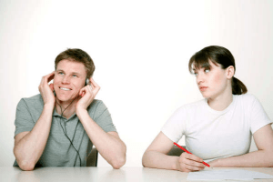 Woman looking at man who is ignoring her by listening on headphones