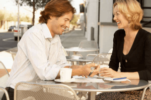 Smiling couple sitting at a table drinking coffer and the woman wondering how to turn on a Taurus man