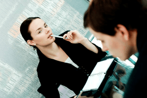 woman hold pen to her mouth while looking longingly at a Virgo man