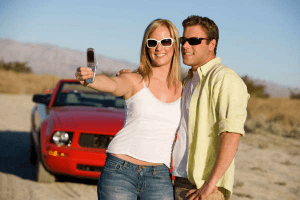 Woman holding a camera at arms length to take a selfie