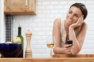 Woman smiling as she leans on her elbow looking at cell phone as she learns how to seduce a Virgo man through text message