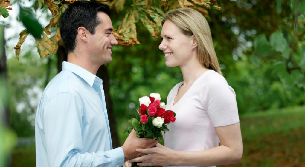 A man giving his girlfriend flowers after he chased him to become a couple