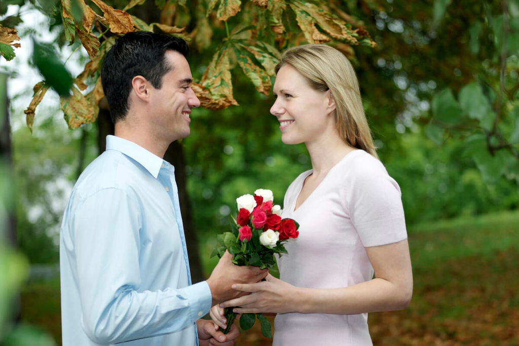 A man in love giving his girlfriend flowers