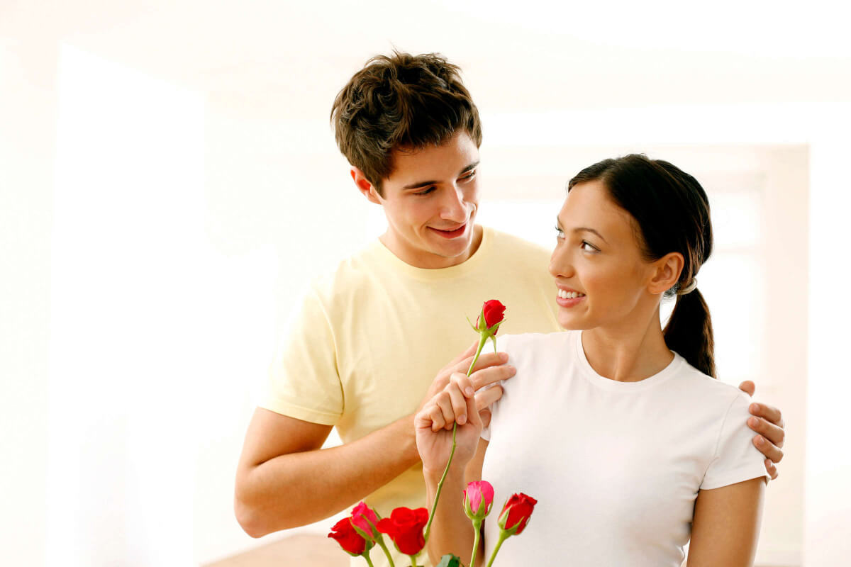 A man giving a woman some roses