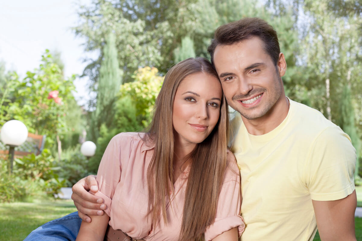 Smiling man with his arm around a woman