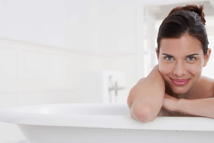 Smiling woman leaning on the edge of the bath confident that she has leart how to turn on a Virgo man