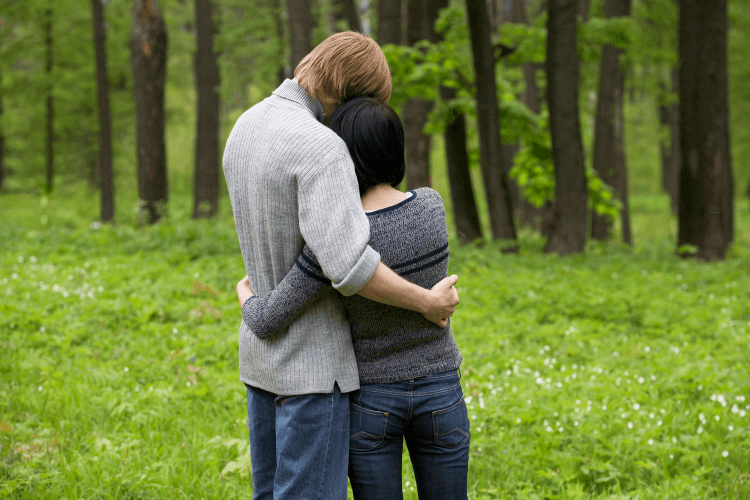 Man with his arms around his Virgo compatibility woman as they look at the distant forest.