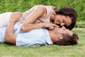 Capricorn man kissing his lover while laying on the grass.