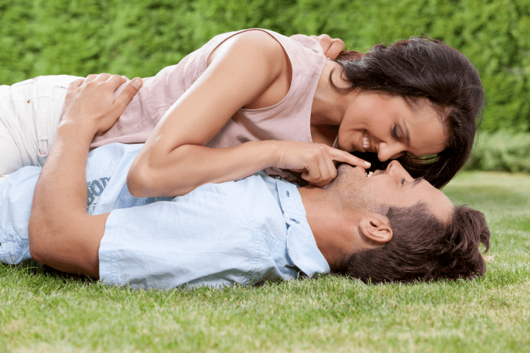 Sagittarius man kissing his lover while laying on the grass.