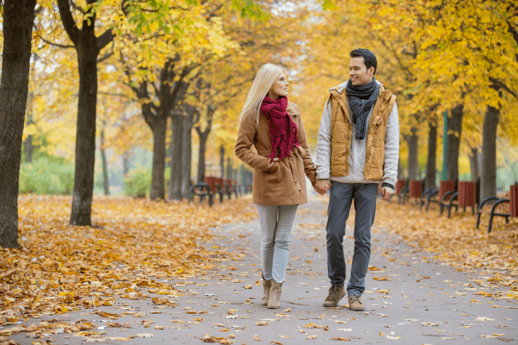 couple holding hands as they stroll through autumn leaves
