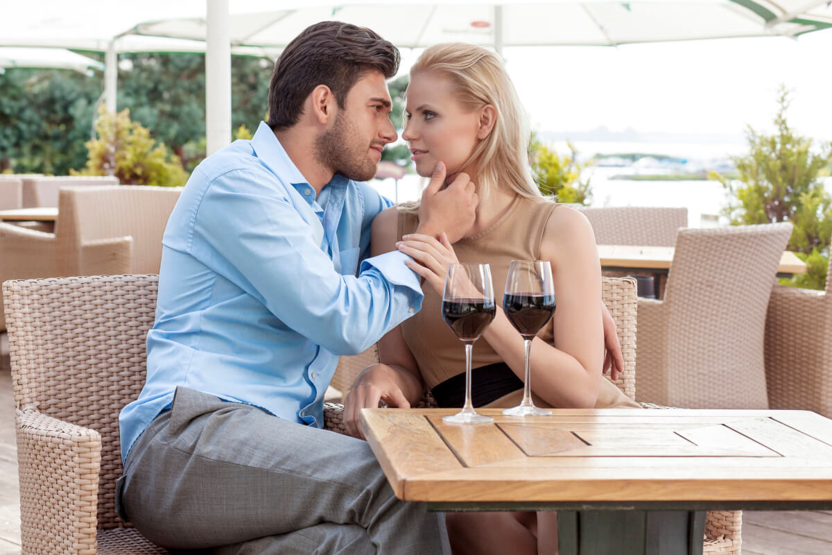 Virgo man caressing the cheek of a blond woman as they drink wine