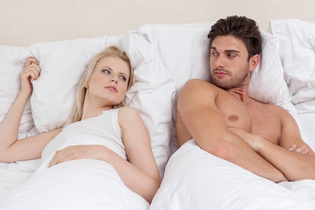 A man in bed with his blond girlfriend