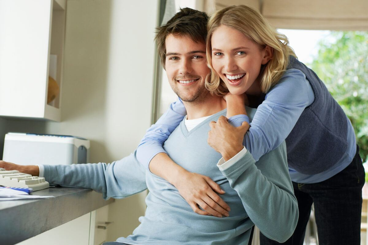 woman with her arms around the neck of a man in a blue sweater
