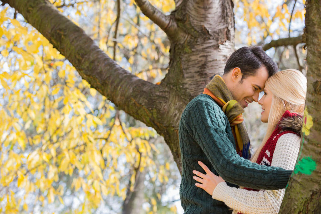 Dating couple kissing while leaning against a tree