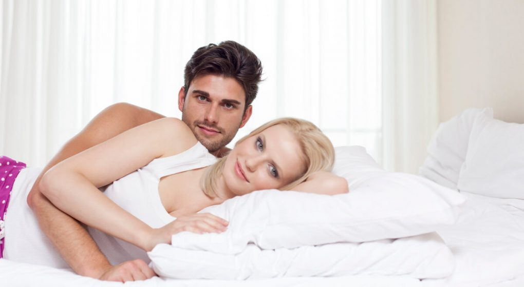 Man in bed with blond woman
