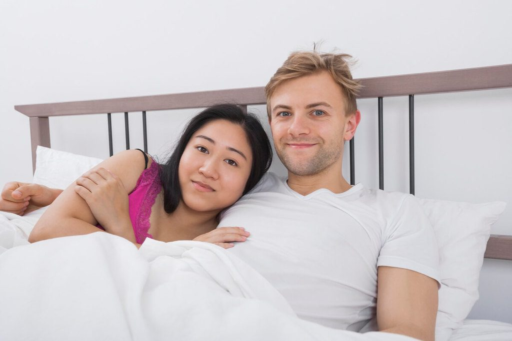 Young man with oriental girlfriend in bed