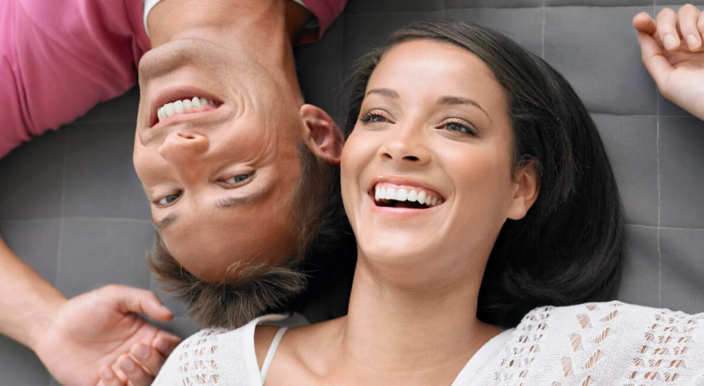 Man lying on the floor with his girlfriend laughing