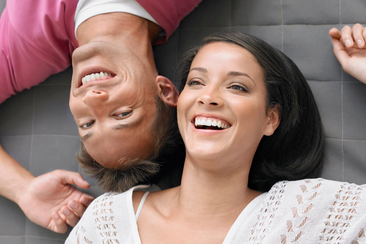 Gemini man lying on the floor with his girlfriend laughing