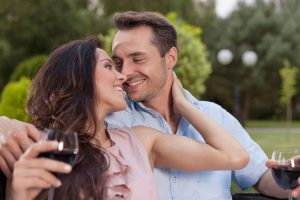 Woman smiling as she strokes the face of her Pisces man
