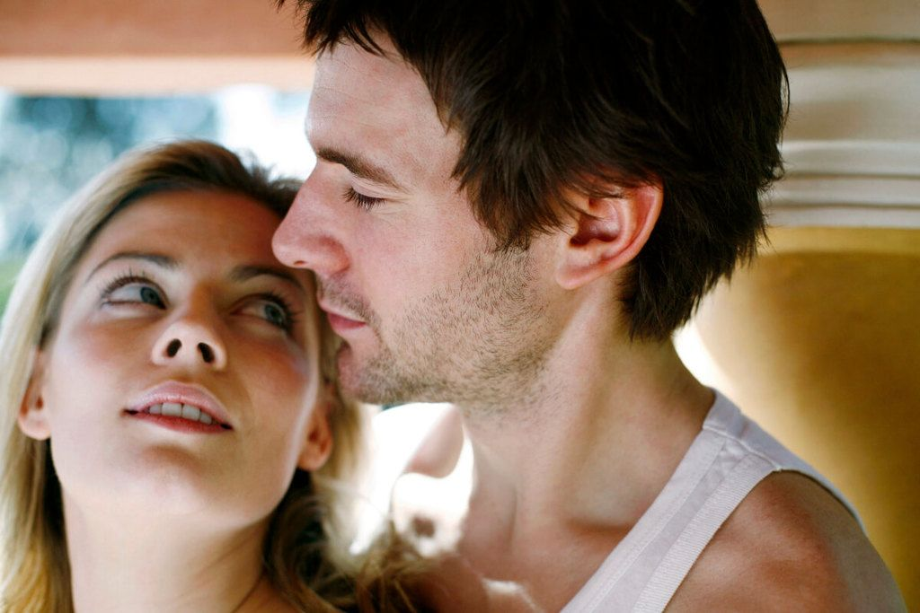 Woman looking up at her Scorpio man who is wearing a vest