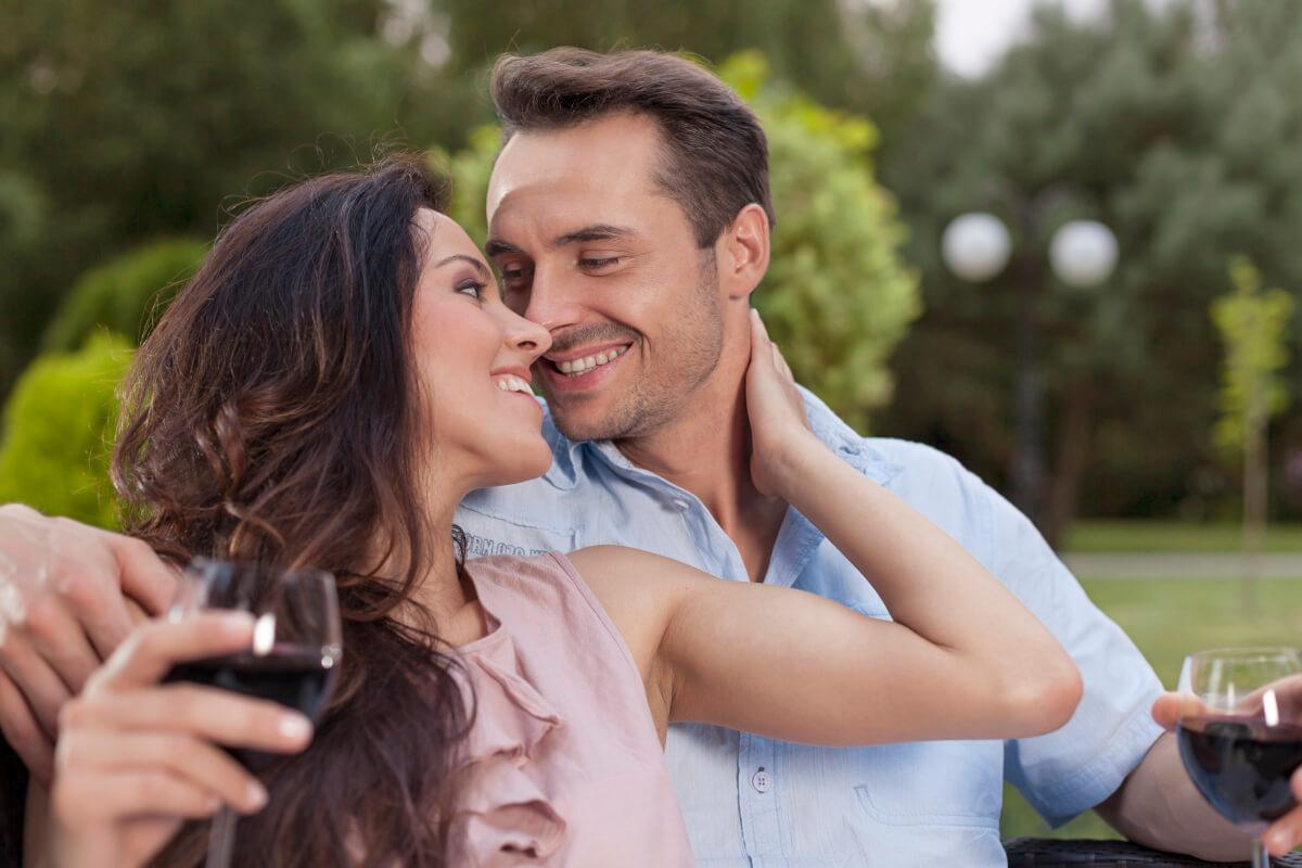 Pisces man being caressed by a woman as they sit and drink wine