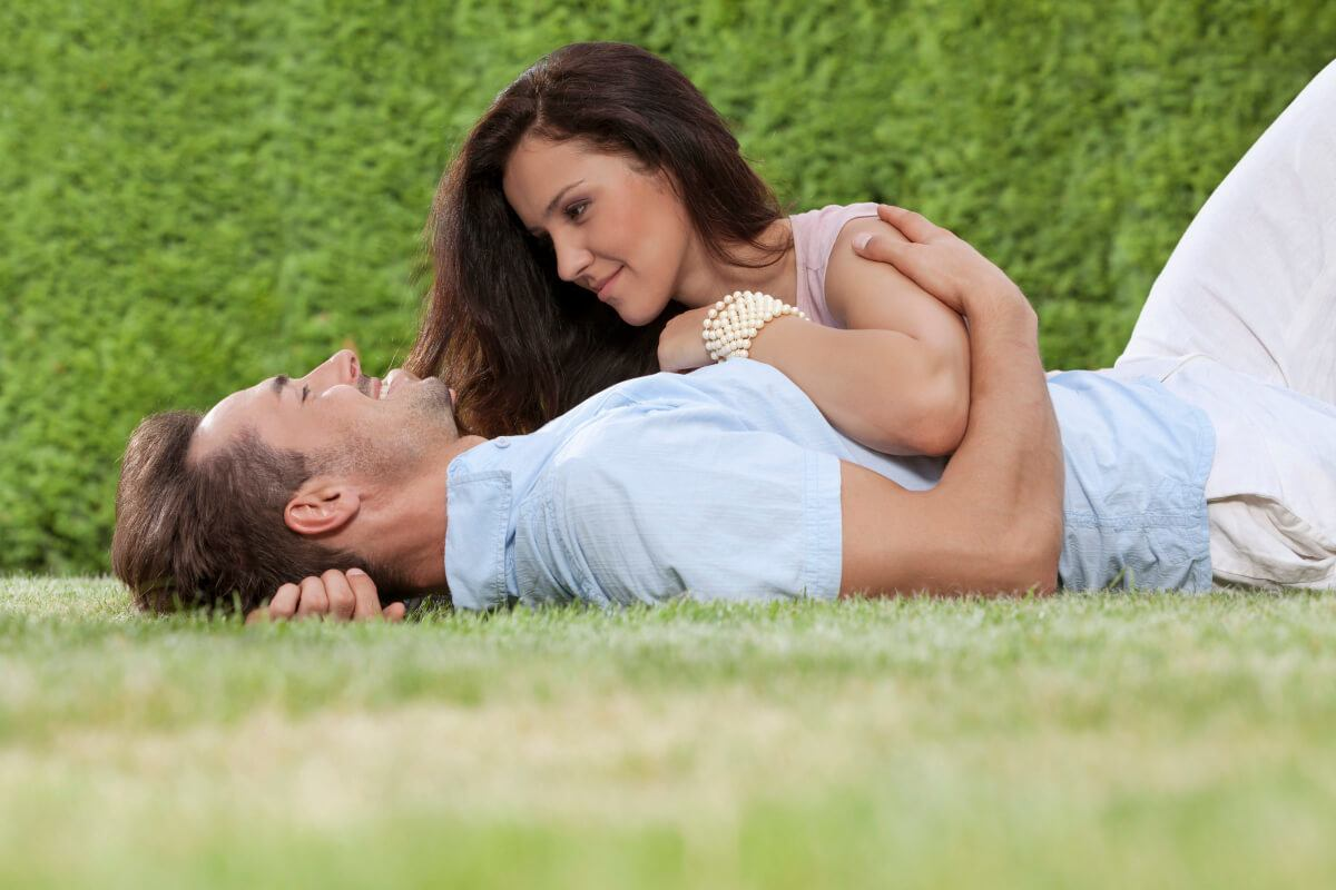 couple cuddling while lying on the grass.