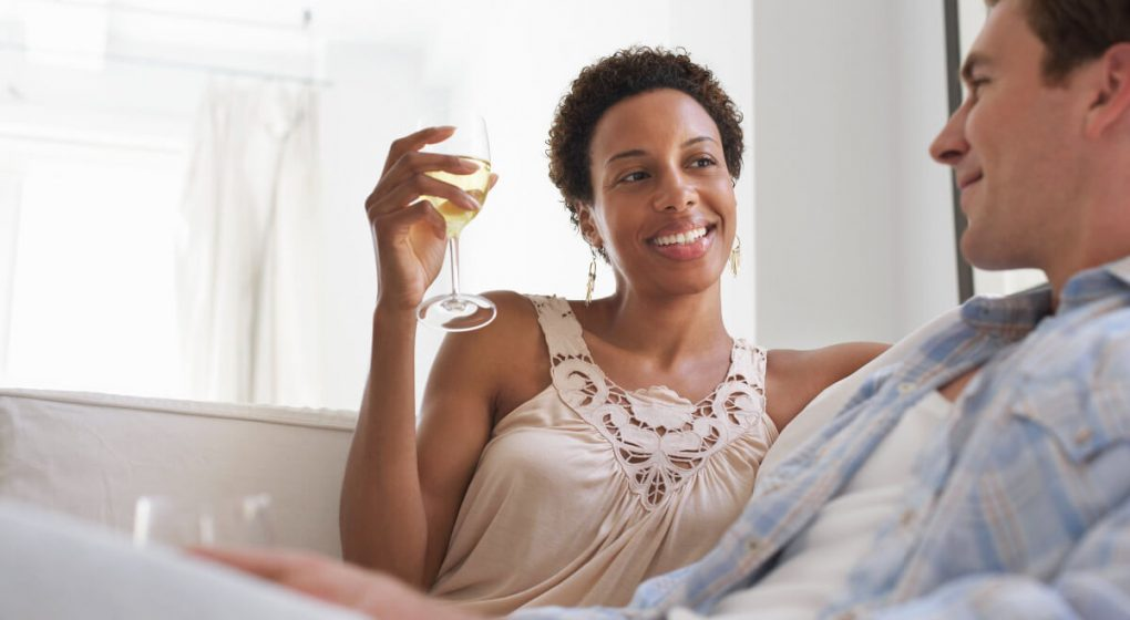 Woman drinking wine talking to a Pisces man while sitting on a couch