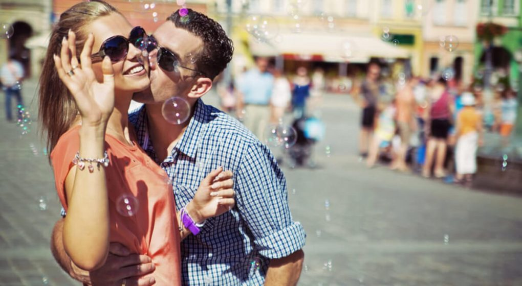 Man kissing woman on the cheek in a cloud of bubbles