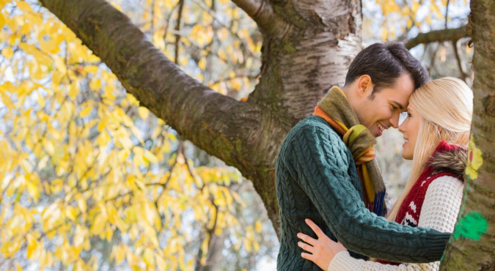 woman leaning against a tree as her Libra man kisses her