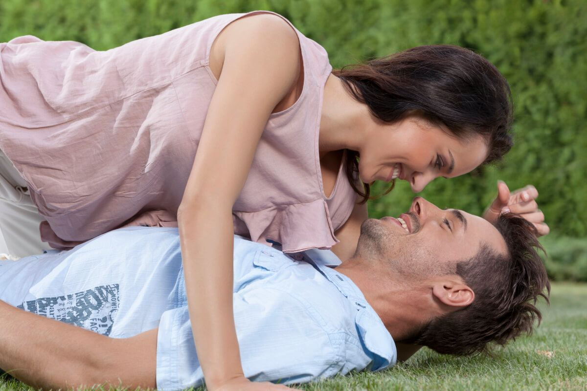 Man lying on his back on the grass while a woman leans down to kiss him