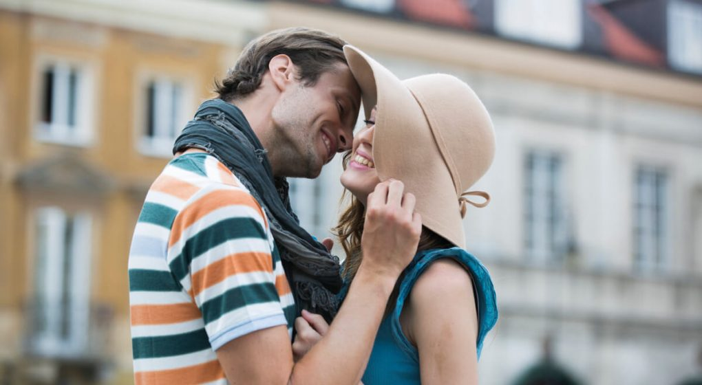 Woman in a large straw hat kissing a Scorpio man
