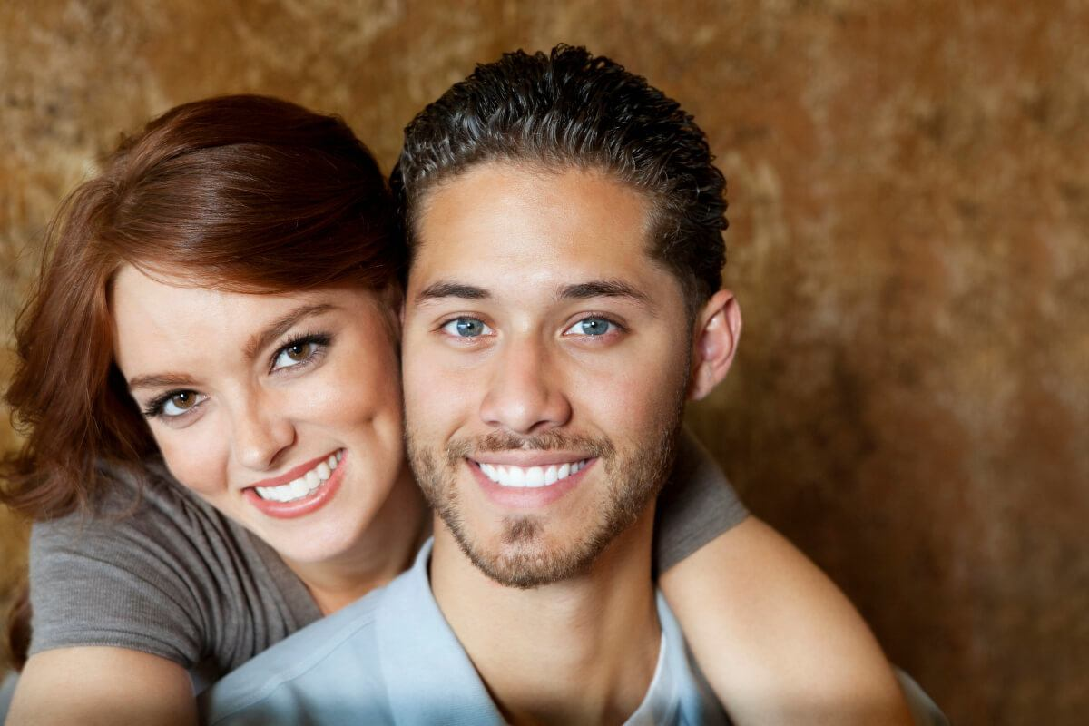 woman standing behind Pisces man with her arms around his neck