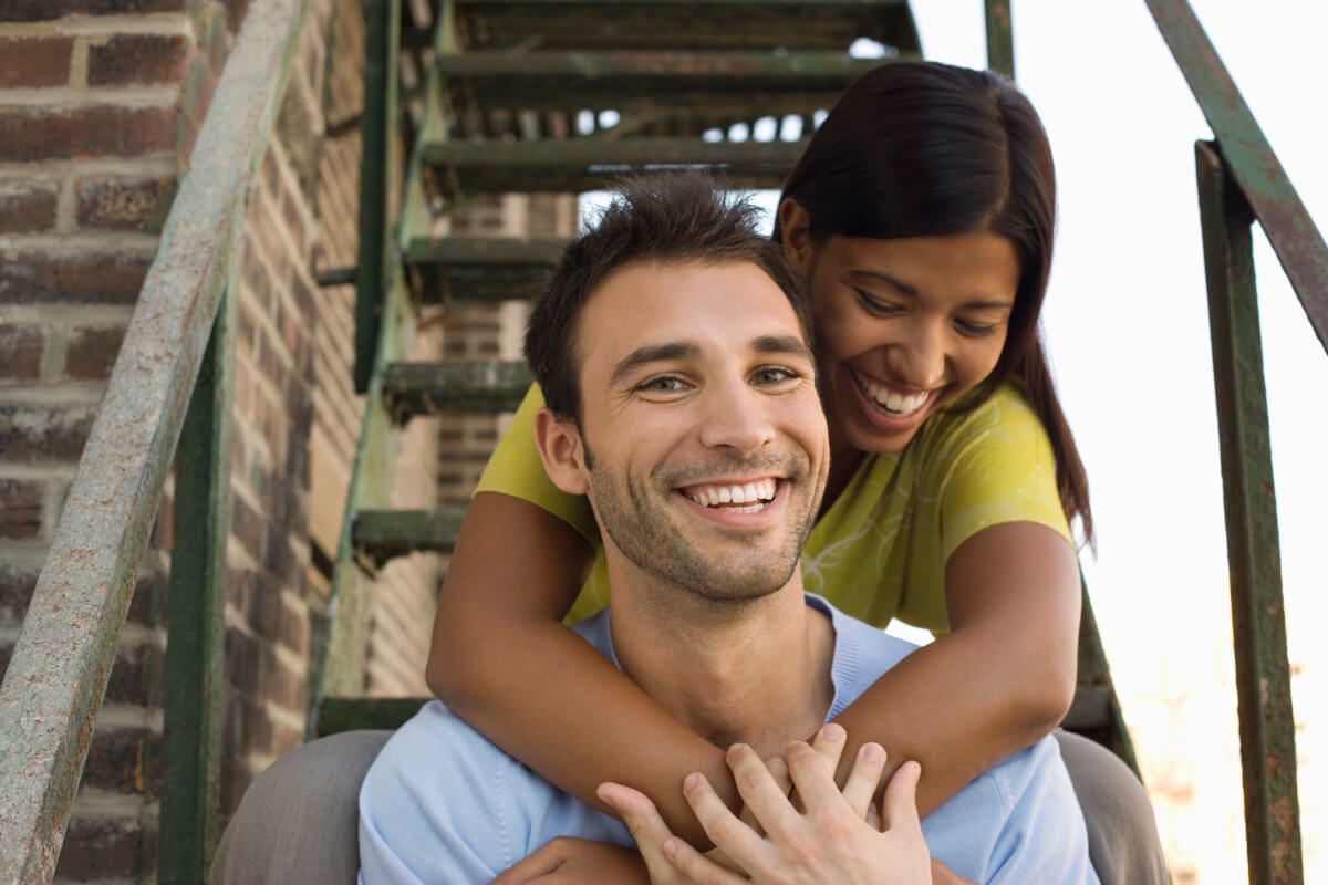Couple smiling as she puts her arms around his neck while sitting on the stairs.