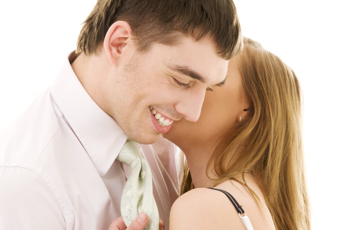 Man smiling as a woman whispers in his ear.