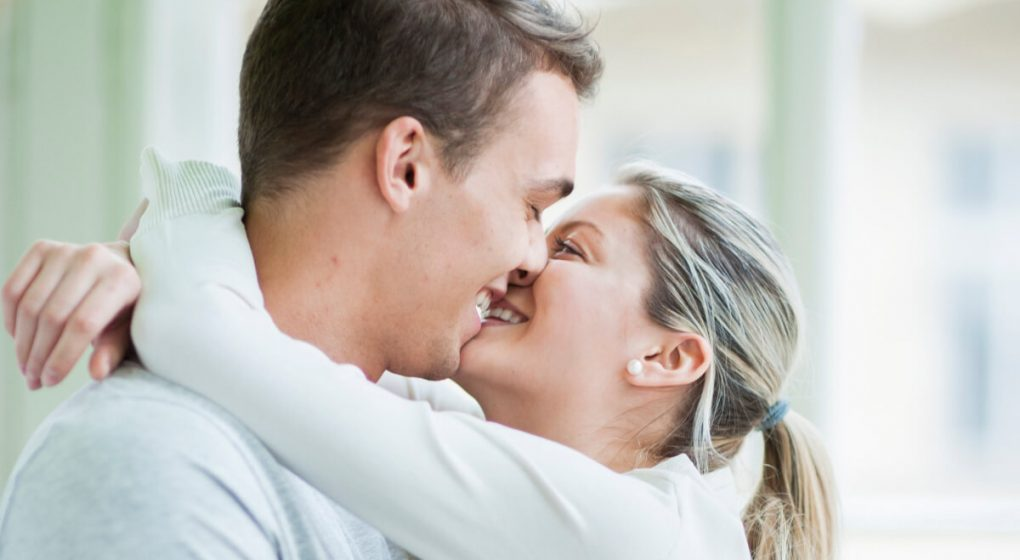 Woman with her arms around a mans neck as she kisses him on the lips
