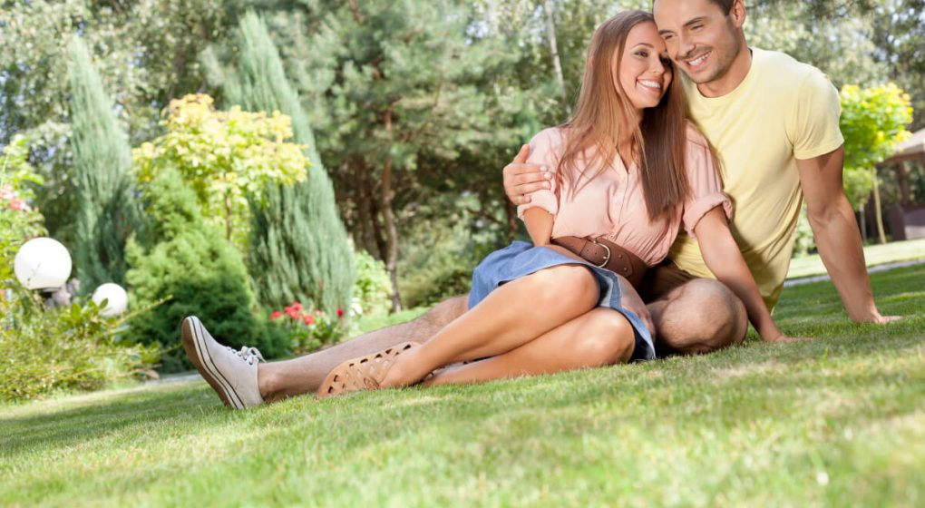 Man with his arm around a woman while sitting on the grass