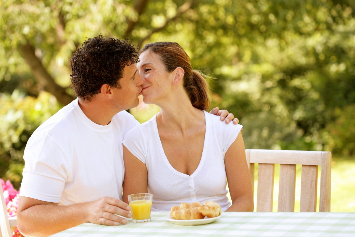 Couple dressed in white kissing and drinking orange juice over breakfast
