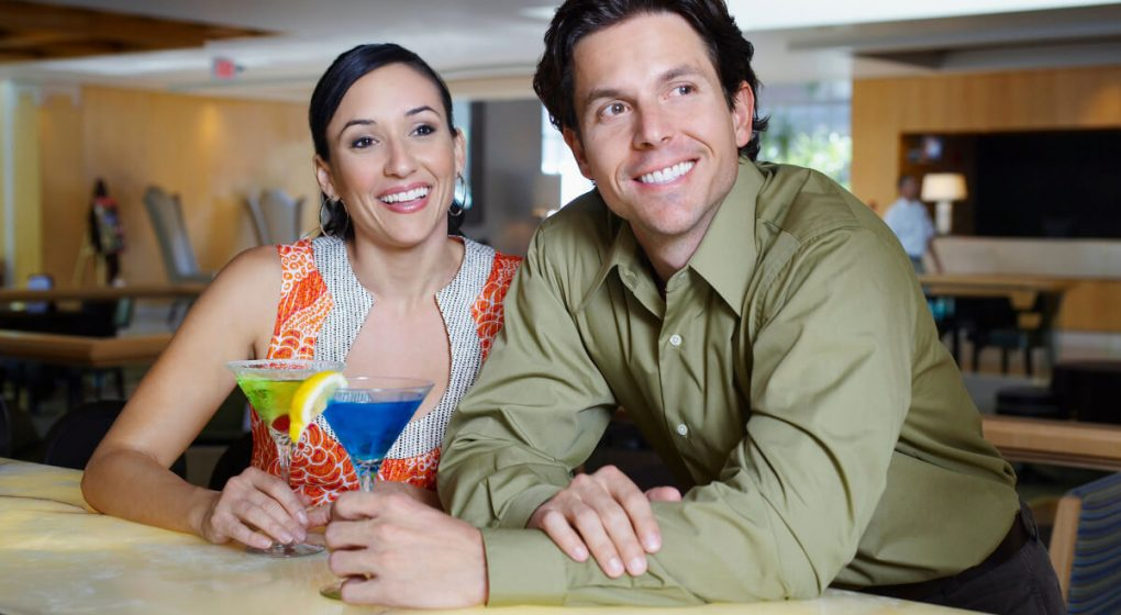 Smiling couple sitting at a bar drinking cocktails